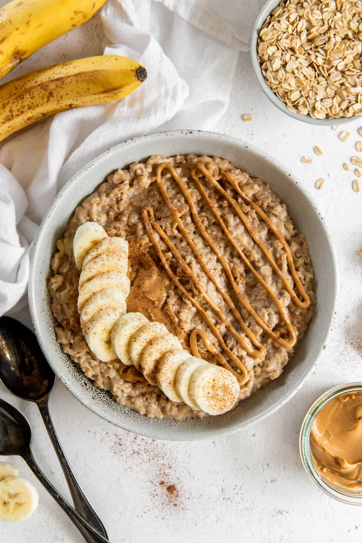 a bowl of peanut butter banana oatmeal with banana slices on top and drizzle of peanut butter