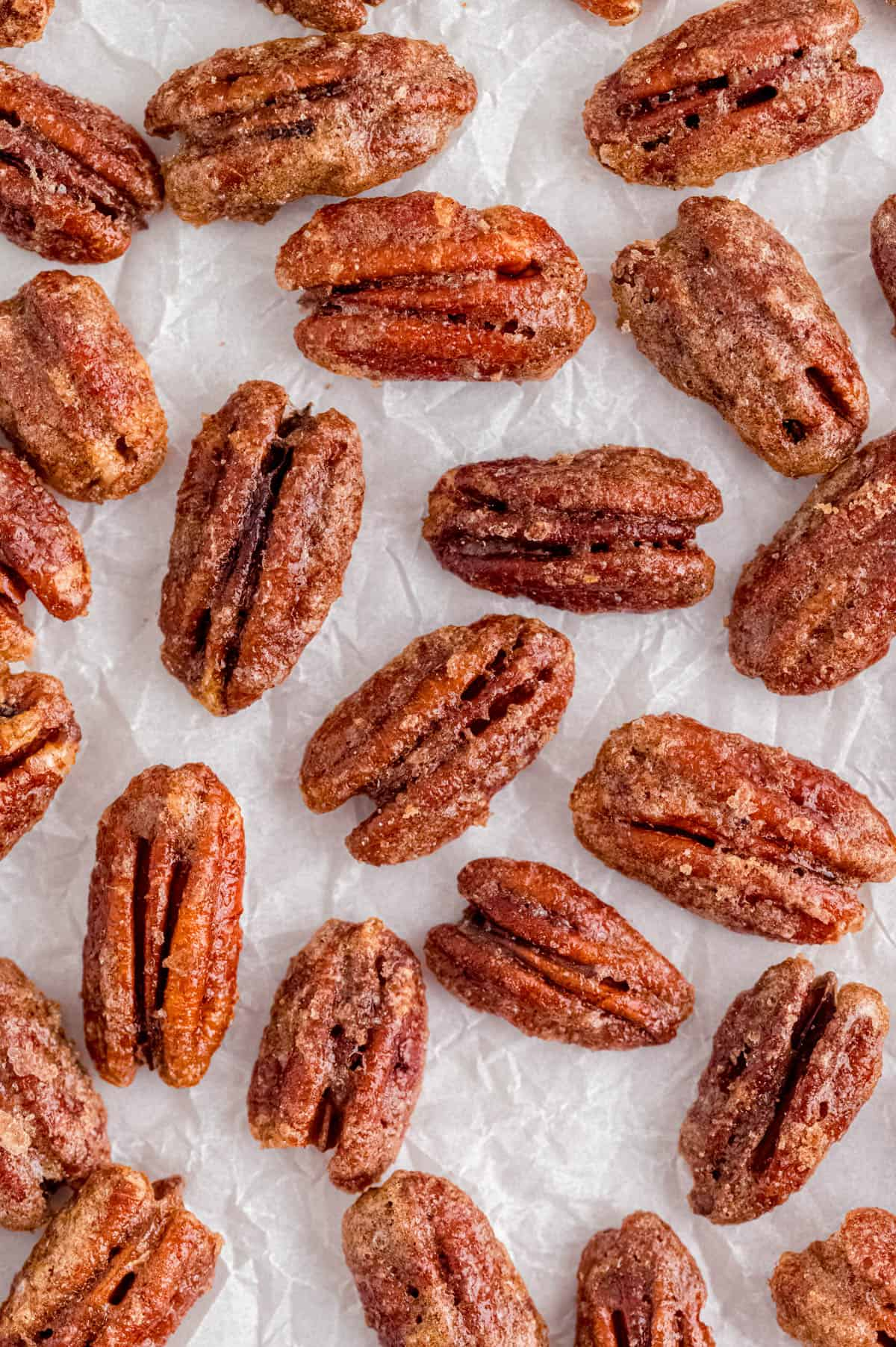 baked candied pecans on a piece of white parchment paper