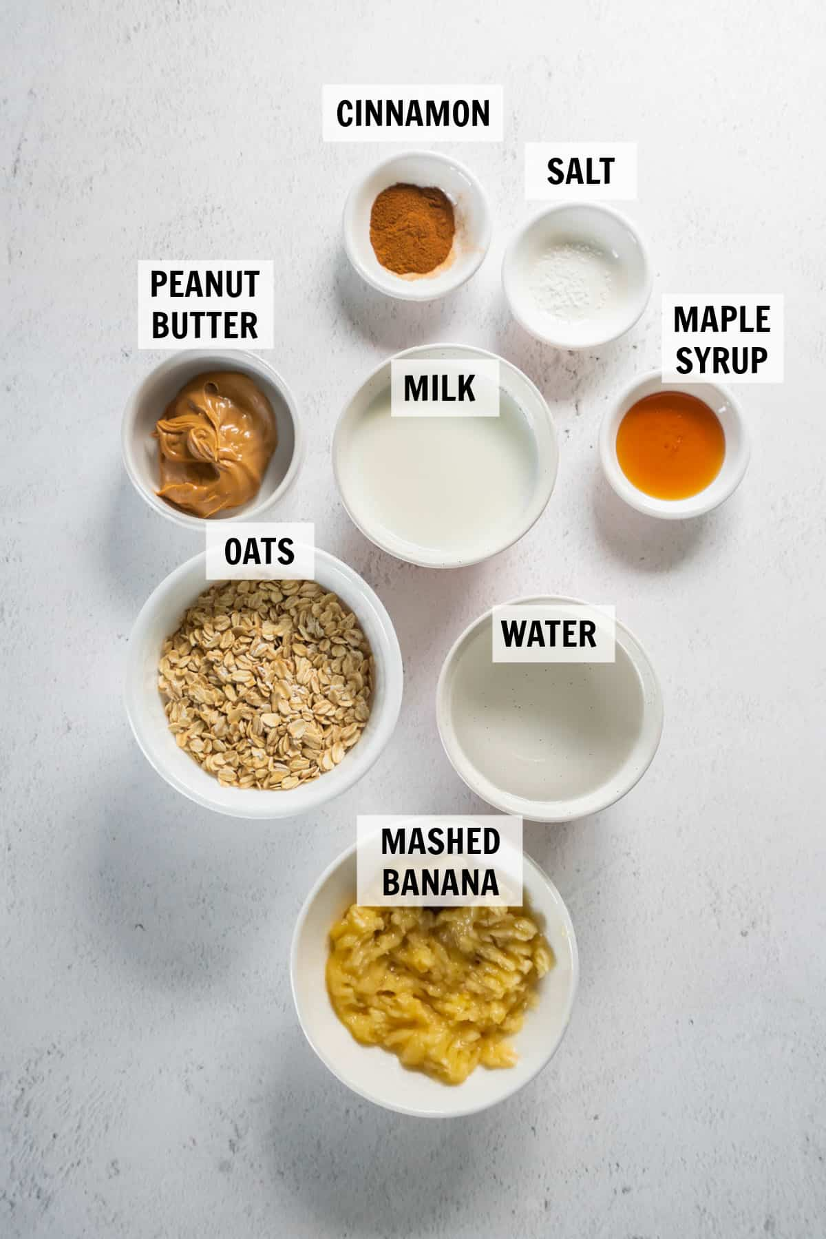 all of the ingredients for peanut butter banana oatmeal on a white countertop