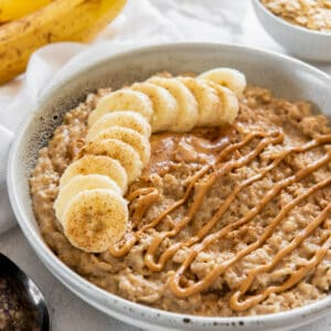a bowl of peanut butter banana oatmeal with peanut butter sauce drizzled on top